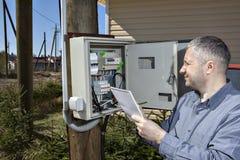 Сельский техник принимая чтение электрического счетчика в стране Стоковые Изображения RF