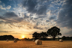 Сельское изображение ландшафта захода солнца лета над полем связок сена Стоковое Фото