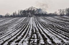 Сельскохозяйственное угодье около дома в сезоне зимы Стоковое Изображение