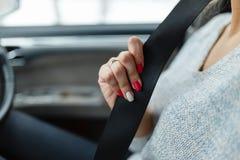 Сжимайте ремень безопасности в руках девушки Девушка водителя прикрепляет ваш ремень безопасности Конец-вверх руки женщины сидя в Стоковое Изображение RF