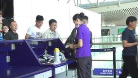 Сиань, Китай - 22-ое сентября 2015 Пассажиры на проверке в счетчике в аэропорте перед полетом видеоматериал