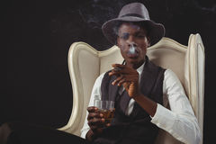 Сигара андрогинного человека куря пока пока сидящ на стуле Стоковое Изображение RF