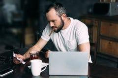 сигара молодого человека куря и смотреть скомканное фото бывший-девушки стоковое фото