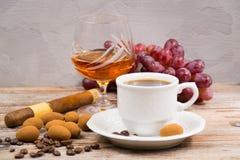 Сигара, рябиновка, эспрессо кофе чашки с яичками шоколада и виноградина Стоковая Фотография RF
