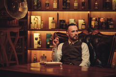 Сигара уверенно человека высшего класса куря в клубе ` s джентльмена Стоковое Изображение RF