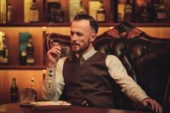 Сигара уверенно человека высшего класса куря в клубе ` s джентльмена Стоковое Изображение
