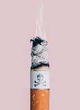 Сигарета горя с символом черепа и косточек Стоковое Изображение