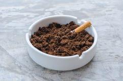 Сигарета и кофейная гуща на керамическом ashtray Стоковое Изображение
