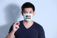 Сигарета молодого человека куря с защитной маской Стоковое фото RF