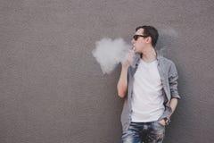 Сигарета молодого человека куря, vaping электронная или vape Серая предпосылка стоковое фото