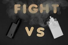 Сигареты против Vape Электронная сигарета над темной предпосылкой Популярные приборы года - современного vaping прибора Стоковое Изображение RF