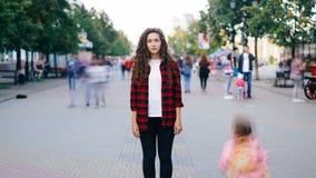 Сигналит внутри промежуток времени красивой девушки при длинное вьющиеся волосы стоя в улице смотря камеру когда много люди и жен видеоматериал