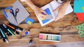 Сигнал-вне чертежа молодой женщины с crayons в тетради делая первоначально коллаж сидя на столе на рабочем месте внутри помещения видеоматериал