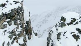 Сигнал тележки на горе покрытой снегом между массивными утесами в 4k акции видеоматериалы