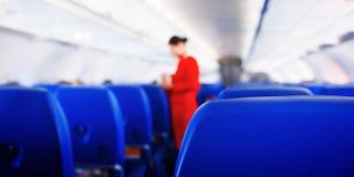 Сиденье пассажира знамени сети в самолете, интерьер самолета и предпосылка stewardess Stewardess представляет обслуживания для па стоковая фотография