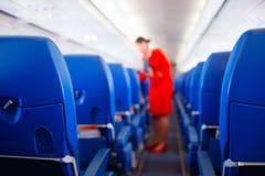 Сиденье пассажира, интерьер самолета при пассажиры сидя на местах и stewardess идя междурядье в предпосылке stewardess s стоковые изображения
