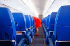 Сиденье пассажира, интерьер самолета при пассажиры сидя на местах и stewardess идя междурядье в предпосылке stewardess s стоковая фотография rf