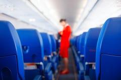 Сиденье пассажира, интерьер самолета при пассажиры сидя на местах и stewardess идя междурядье в предпосылке stewardess s стоковая фотография