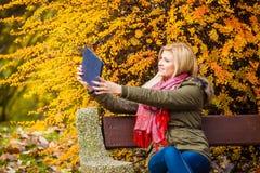 Сидеть женщины ослабляя на стенде в парке используя таблетку Стоковые Фото