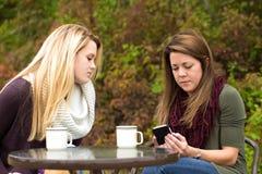 Сидеть женщины отправляя СМС и говоря снаружи осенью стоковые изображения