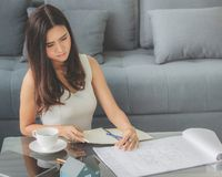 Сидеть красивой азиатской девушки усмехаясь работающ дома дизайн с стоковые фото