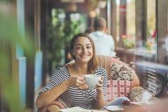 Сидеть молодой женщины крытый в городском кафе Стоковое фото RF