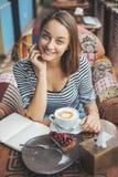 Сидеть молодой женщины крытый в городском кафе Стоковое Изображение RF