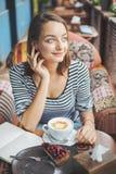 Сидеть молодой женщины крытый в городском кафе Стоковые Фото