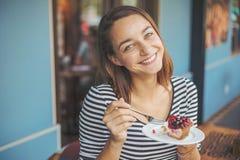 Сидеть молодой женщины крытый в городском кафе Стоковая Фотография