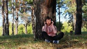 Сидеть молодой женщины отдыхая деревом в парке и слушать к музыке через наушники Музыка, внешнее воссоздание сток-видео