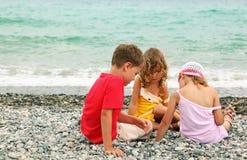 сидеть сестер брата пляжа стоковые фото