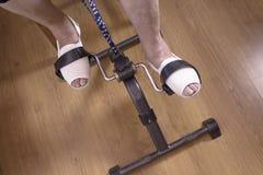 Сидеть старшей женщины pedaling на стуле Стоковые Фотографии RF