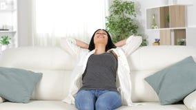 Сидеть счастливой женщины ослабляя на кресле дома сток-видео