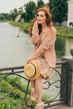 сидит на загородке, в руках шляпы, бежевого платья в цветке и бежевого свитера красный цвет красивейшей девушки с волосами изобра стоковое изображение