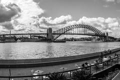 Сидней, Австралия - 12-ое января 2009: Взгляд прогулки Сиднея с ослабляя людьми Мост гавани увиден через воду стоковые изображения