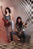 Сидя и стоя женщины с электрической гитарой Стоковые Изображения