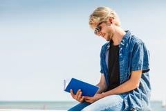 Сидя книга чтения человека снаружи на солнечный день стоковая фотография rf