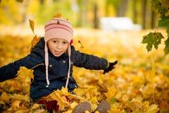 Сидя маленькая девочка шаловливо брошенная прочь над его головой покрасила кленовые листы Милый ребенок имея потеху в парке осени стоковые фотографии rf