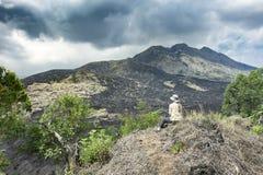 Сидя турист девушки на крае холма и взглядах на черных утесах лавы и драматическом облачном небе Панорамный вид наклонов  стоковое фото
