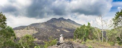 Сидя турист девушки на крае холма и взглядах на черных утесах лавы и драматическом облачном небе Панорамный вид наклонов  стоковое изображение