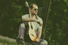 Сидя человек с гитарой с солнечными очками стоковые изображения