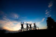 Силуэты велосипедистов стоя на холме Стоковая Фотография RF