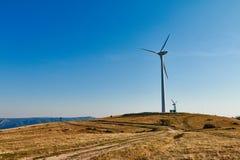Силуэты ветротурбины против голубого неба, луга вершины холма Стоковое фото RF