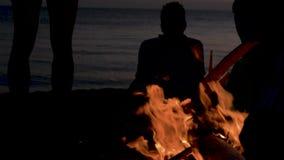 Силуэты группы людей с детьми против захода солнца и огня моря горящего на пляже Лагерный костер на видеоматериал