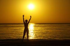 Силуэты девушки с поднятыми руками против предпосылки восхода солнца на морском побережье стоковые фотографии rf