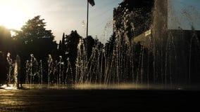 Силуэты детей играют в фонтане города на летний день 4K видеоматериал
