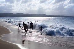 Силуэты детей и людей играя на пляже в волнах и воде брызгают на каникулах, голубом море, свете солнца волн стоковое изображение