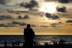 Силуэты женщины при ребенок и люди наблюдая красивое Стоковая Фотография