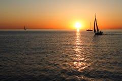 Силуэты золота шлюпок на море Стоковые Изображения