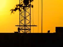 Силуэты крана и рабочий-строителей на предпосылке захода солнца стоковое фото